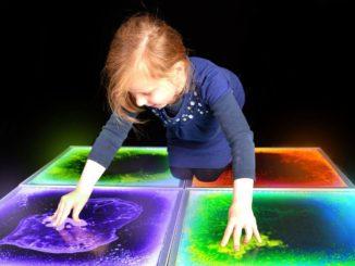 девочка играет с жидкой плиткой
