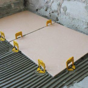 две плитки рядом и зажимы в системе выравнивания плиток